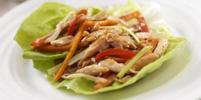 A Wrap Of Cabbage, Chicken, And Assorted Vegetables Sits On A White Plate.