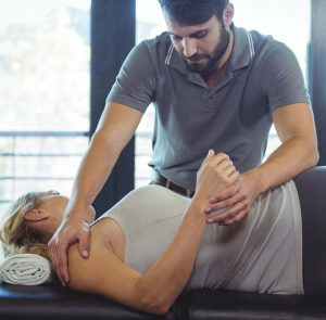 A Standing Male Chiropractic Doctor Adjusts A Female Patient Lying On Her Side.