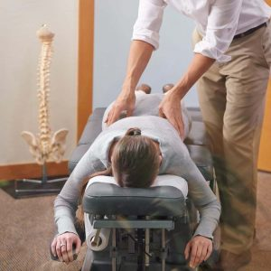 A Female Chiropractic Doctor Stands Over A Female Patient Lying Facedown To Adjust Her Back.