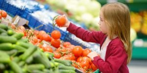 Little girl in grocery store holding a tomato making healthy eating choices