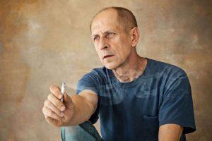 Worried mature man sitting at studio, smoking and thinking about something