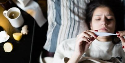 woman lying in bed with a fever, looking at a thermometer with tissues and a mug of hot drink next to her