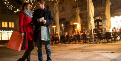 man and woman look at each other an smile while standing together at an outdoor mall, at night, during the holidays