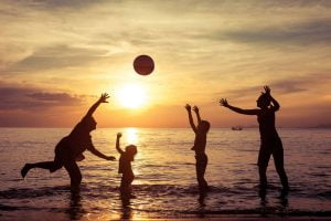 family playing with a ball on the beach