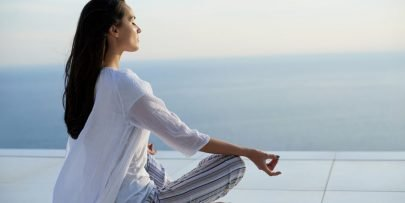 young woman practice yoga meditation on sunset with ocean view in background