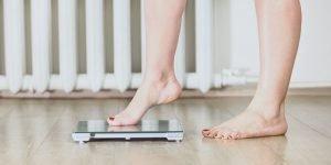 woman steps onto a bathroom scale barefooted